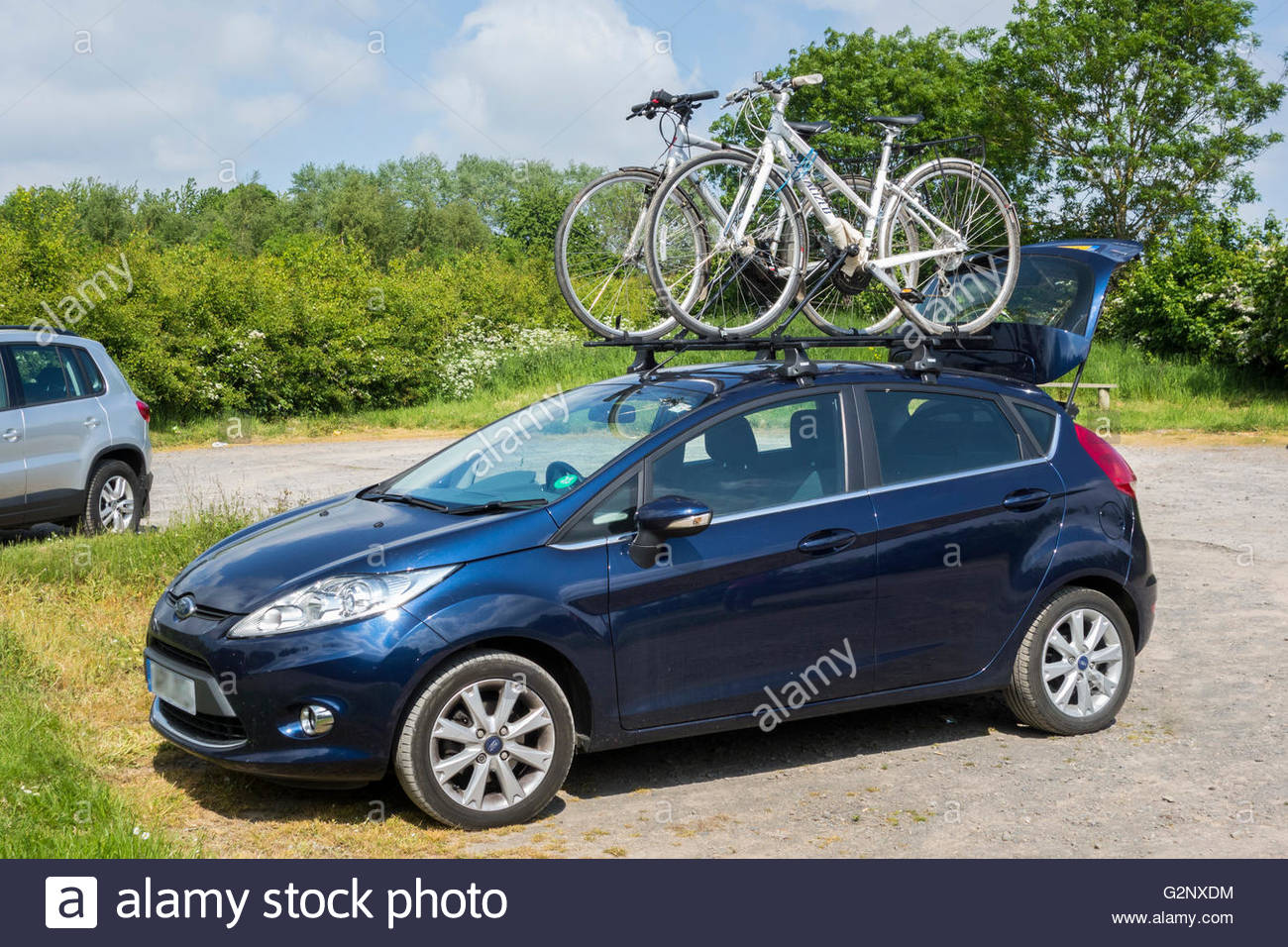 A Ford Fiesta car carrying two bikes on a roof rack Stock