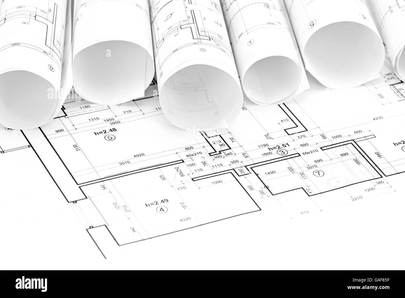hight resolution of architectural blueprint rolls and floor plans on desk