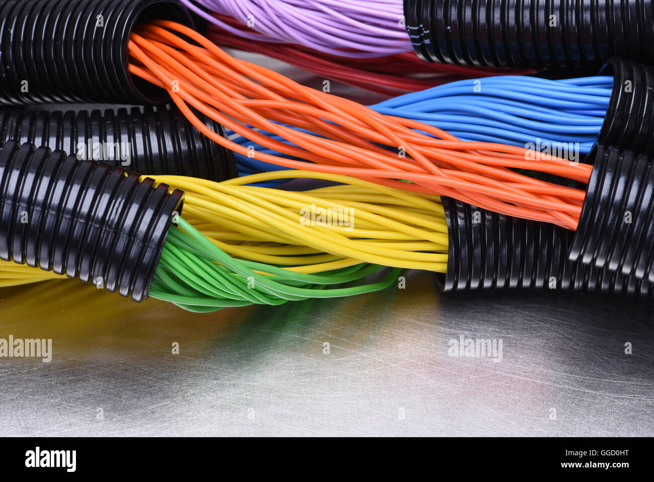 hight resolution of colorful electric cables and wires in corrugated black plastic pipes used in electrical installation on metal surface as background