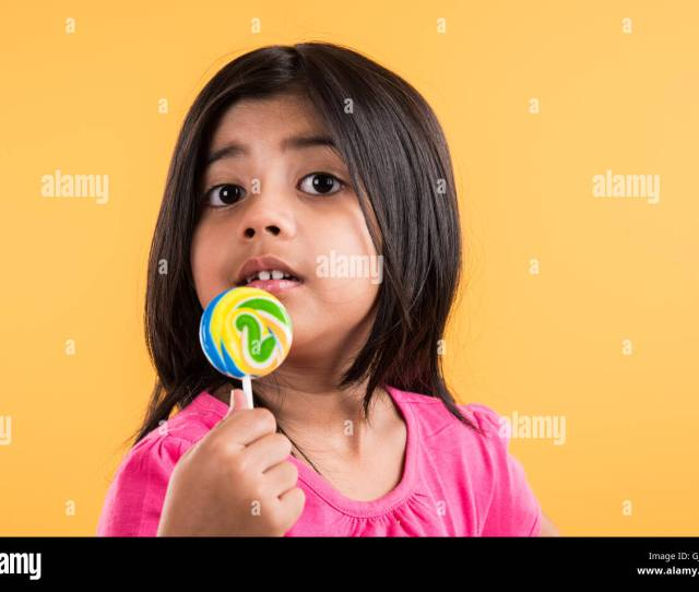 Indian Small Girl With Lolipop Or Loly Pop Asian Girl And Lolipop Or Lolypop Playful Indian Cute Girl Posing With Lolipop