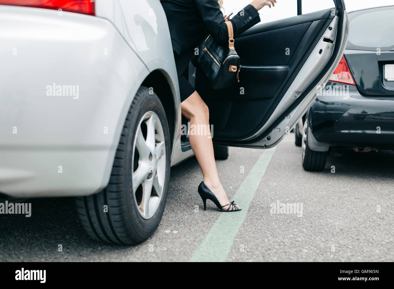 Woman Wearing High Heels Getting Out Of Car Stock Photo