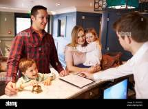 Family Checking In Hotel Reception Desk Stock
