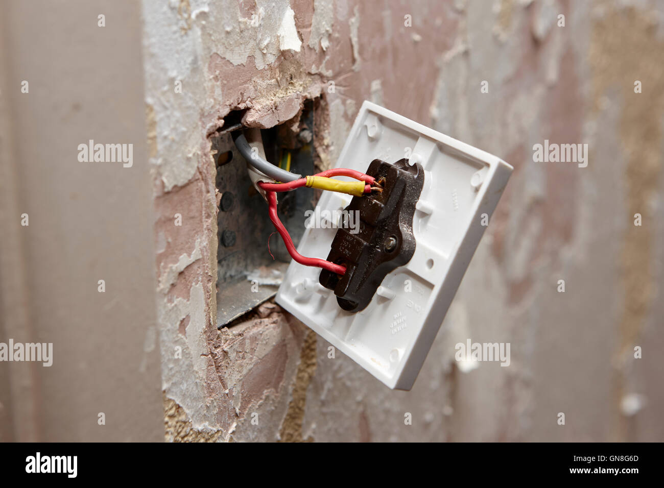 hight resolution of bare wiring on back of light switch in house being redecorated in the uk