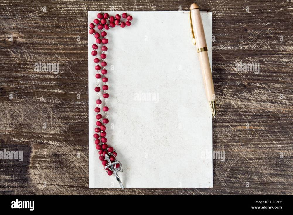 medium resolution of catholic rosary and pen on blank paper sheet with copy space stock image