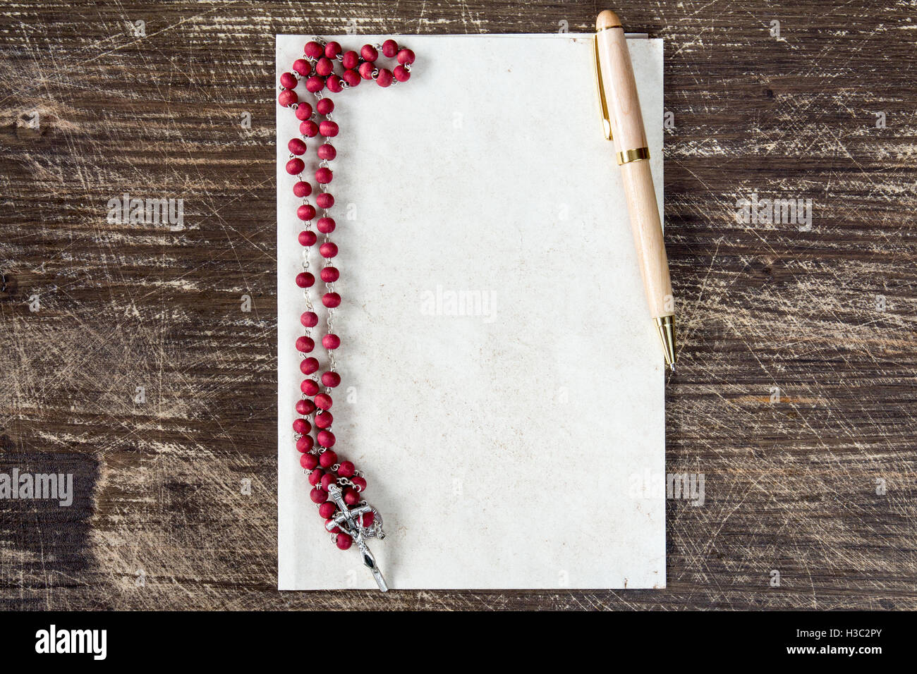 hight resolution of catholic rosary and pen on blank paper sheet with copy space stock image