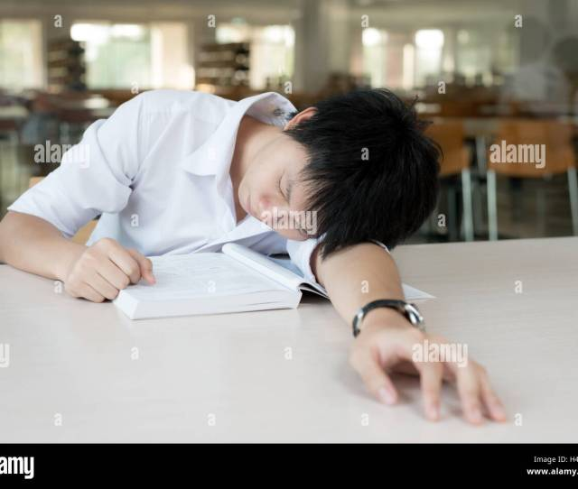 Tired Asian Student Or Asian Young Man With Books Sleeping In Library At University Student Education Session Exams