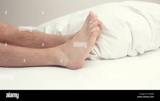 Closeup Of Hairy Legs And Feet Of Man In Bed In White Bedsheets Stock Image