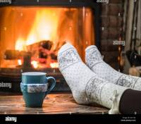 Warming and relaxing near fireplace. Woman feet near the ...