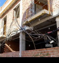 unsafe electrical wiring tangled up outside a house under development [ 1300 x 956 Pixel ]