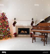 Living room with glowing fireplace, grand piano and ...