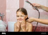 Seven-year girl bathe in a bath under the shower Stock ...