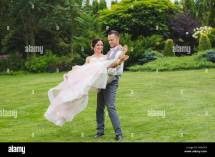 Groom Holding Beautiful Bride In Arms Outdoors. Pink