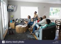 African American family watching TV in living room Stock ...
