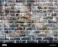 Section of red brick wall with distressed black painted ...