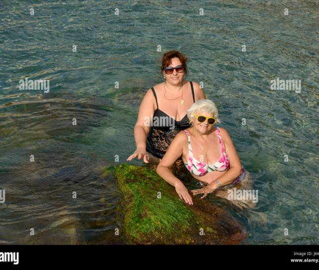 Two Women Senior Blonde And Mature Plump Brunette Are Posing In Clear Water Of Sea Shallow Near Algae Covered Stone