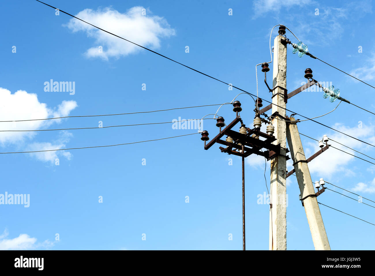 hight resolution of aged electricity pylon with cables and insulators shot against a blue summer sky with white clouds