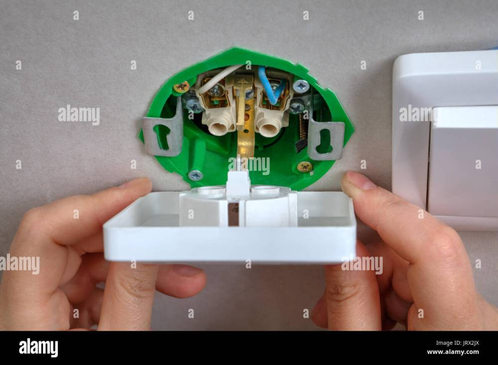 medium resolution of installing the wall outlet into a wiring box close up hands of an electrician