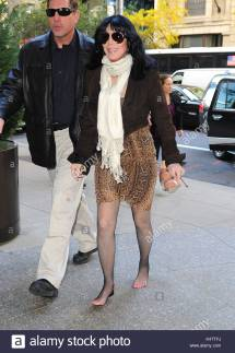 Cher. Cher Walking Barefoot Carrying Shoes In