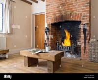 A blazing fire in a red brick fireplace in the living room ...