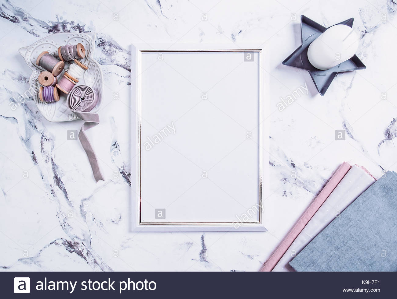 hight resolution of blank photo frame and spool of threads buttons a stack of fabrics over marble table background mockup flat lay top view