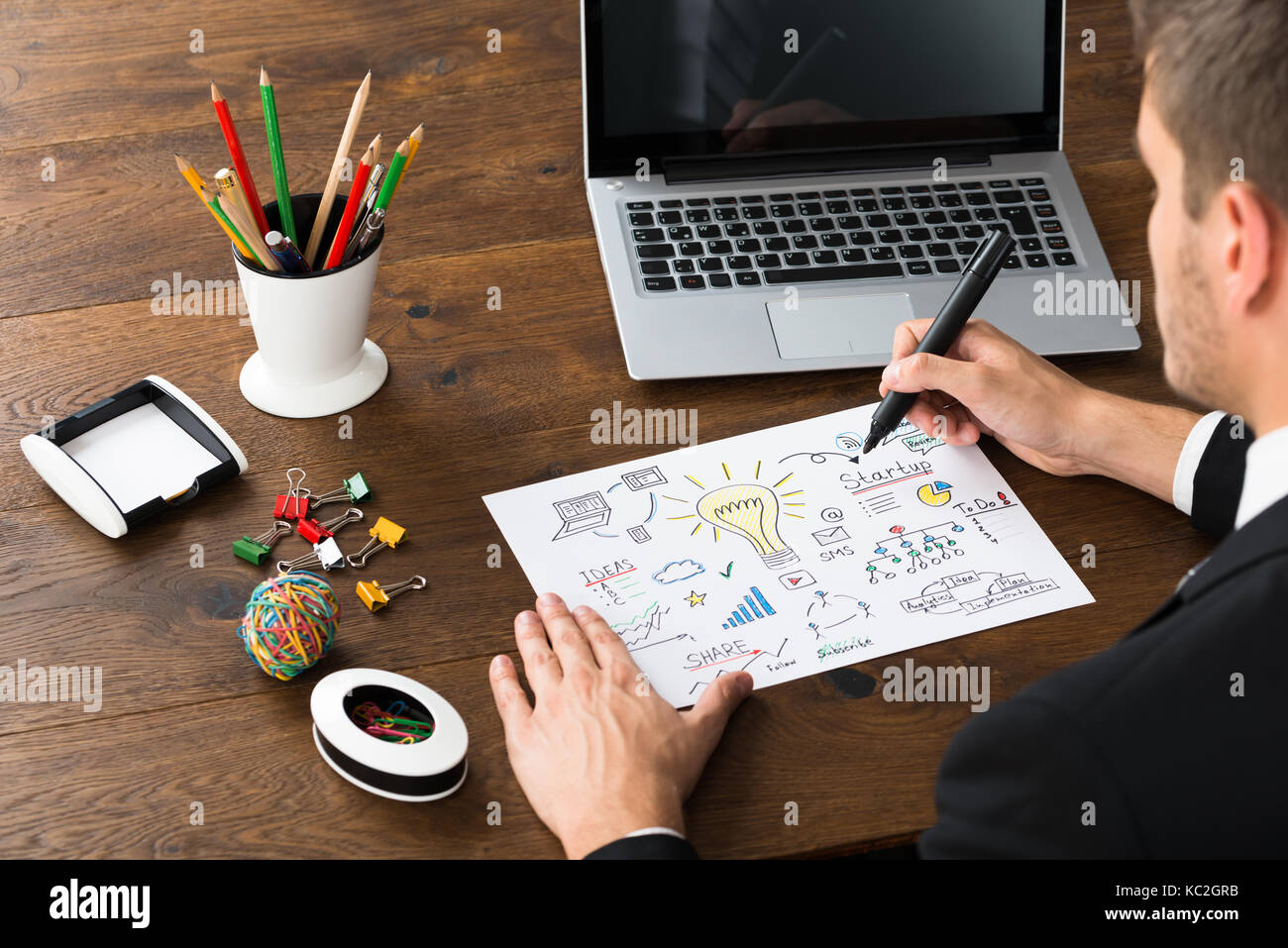 hight resolution of close up of businessman with office supplies and laptop drawing diagram of start up plan at desk