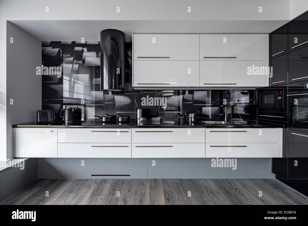 Modern Kitchen With White Cupboards And Black Wall Tiles Stock Photo Alamy