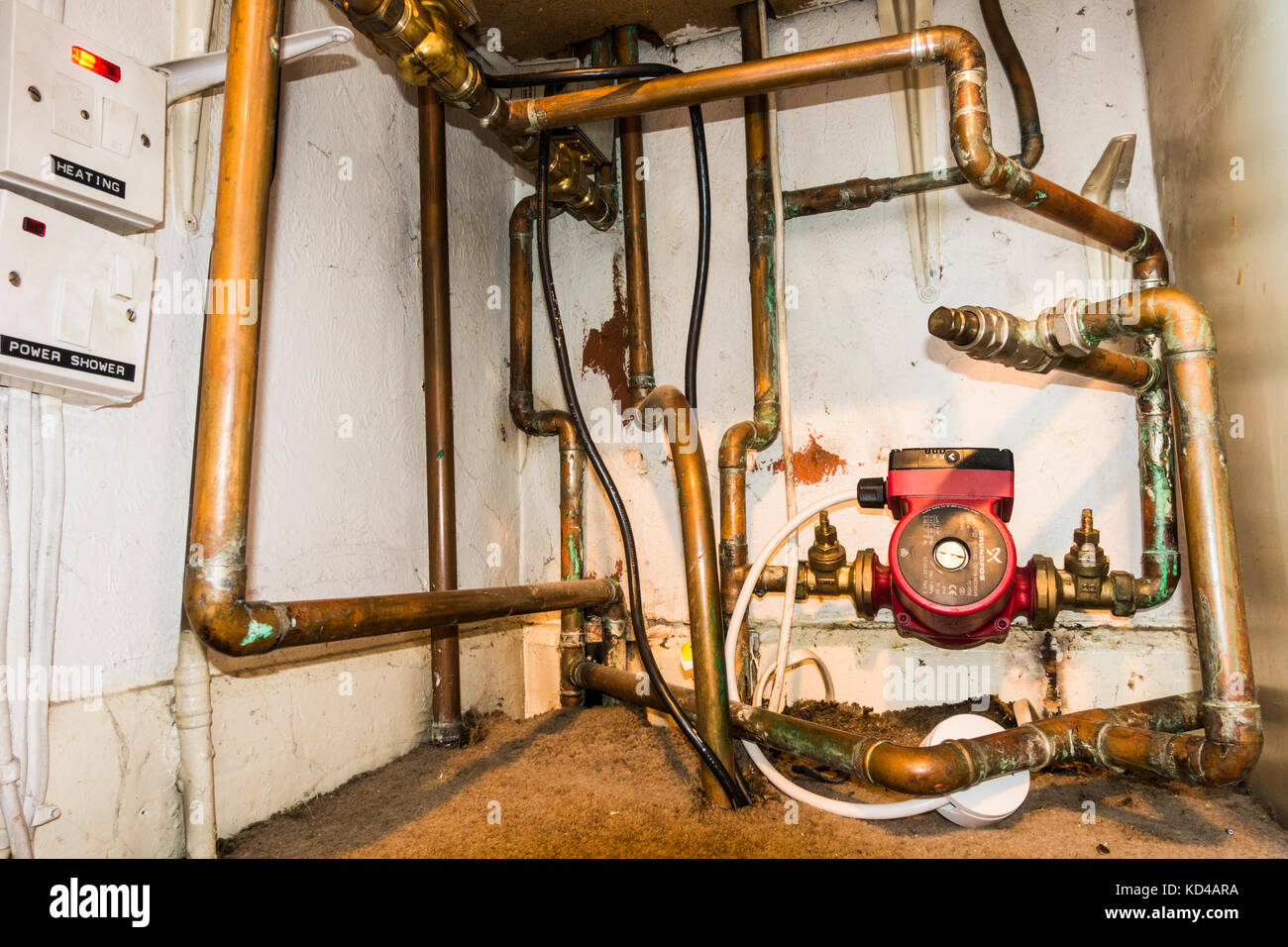 hight resolution of domestic installation of a central heating system with wide view of pump wiring and copper pipework inside a cupboard of a home in england uk