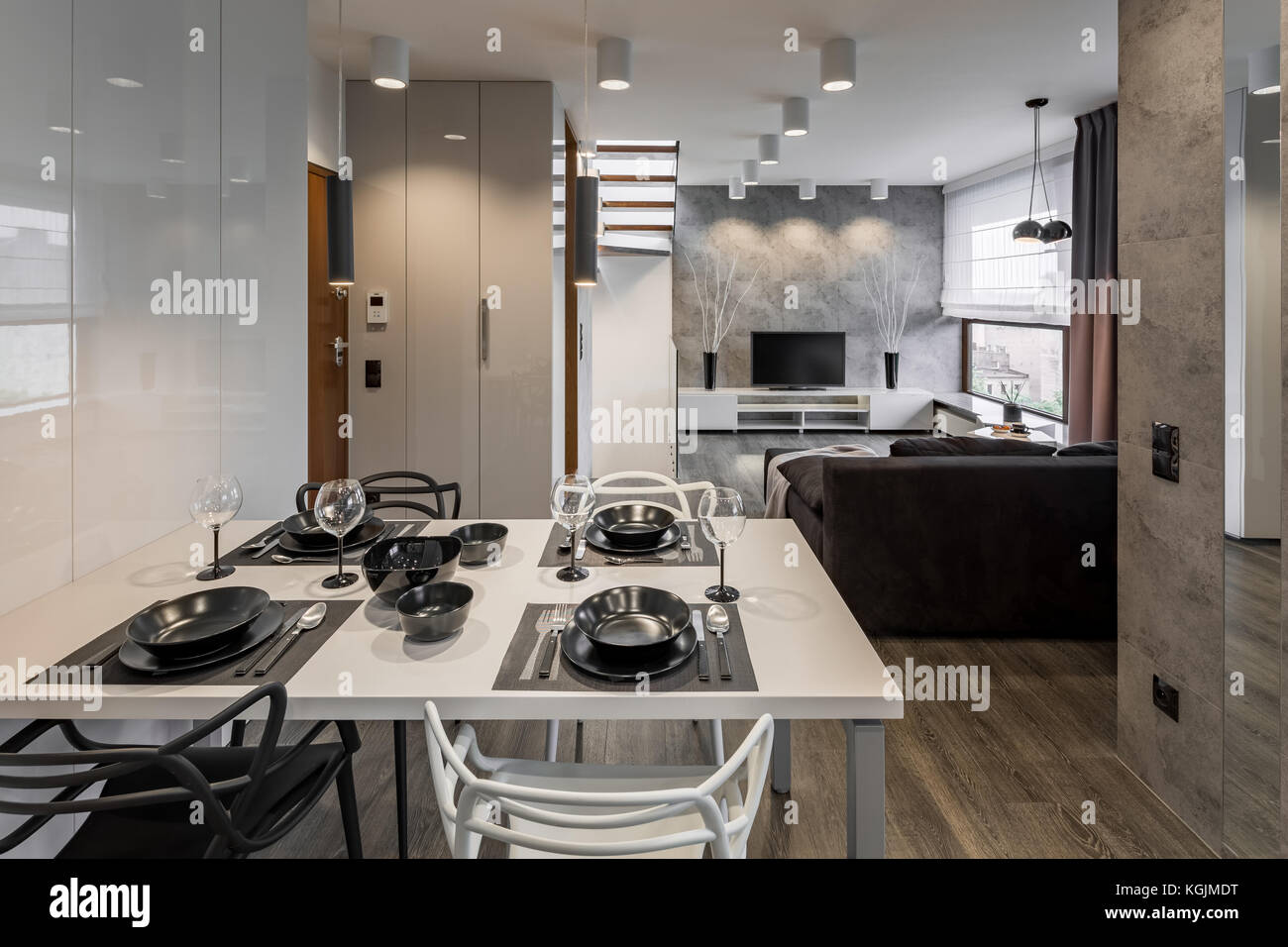 Modern Apartment With White Table And Black Dinnerware Stock Photo Alamy