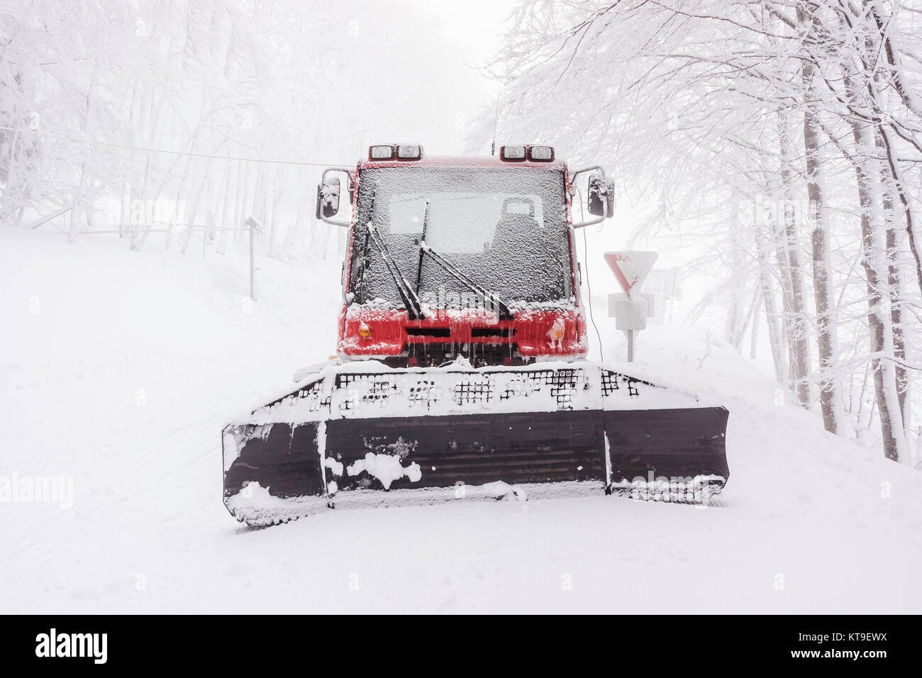hight resolution of front view of a snowy snow plow in winter on a foggy day vosges
