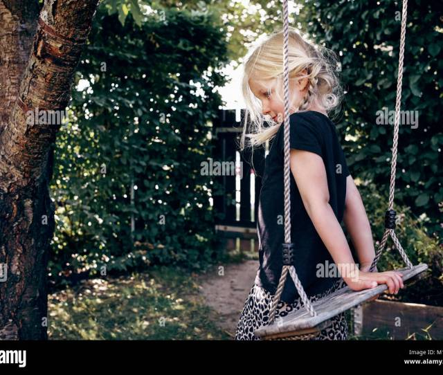 Shy Little Blonde Girl Playing By Herself On A Tree Swing In Her Backyard On A