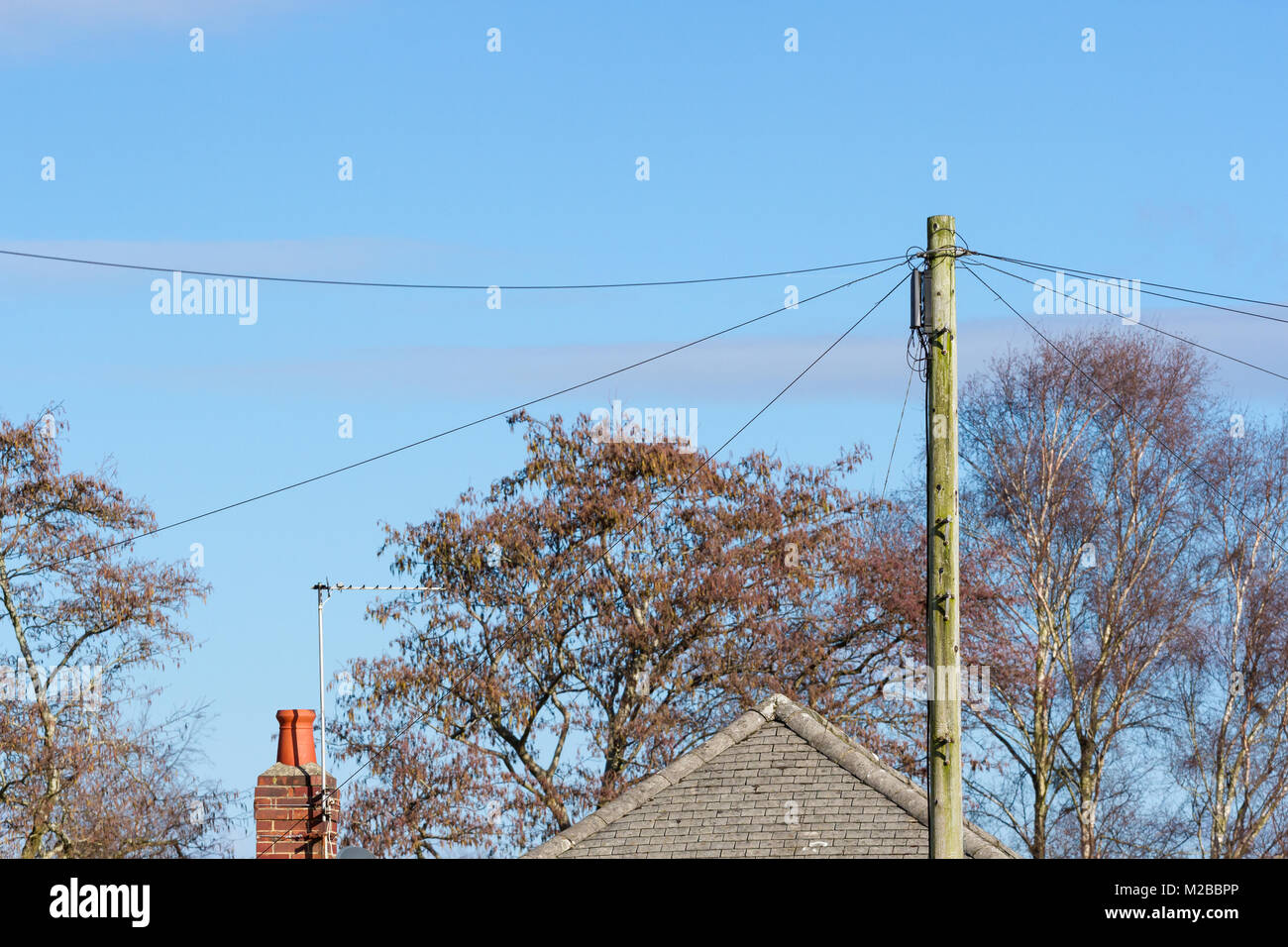 hight resolution of the top of a telephone pole with phone lines connected in a residential area united kingdom