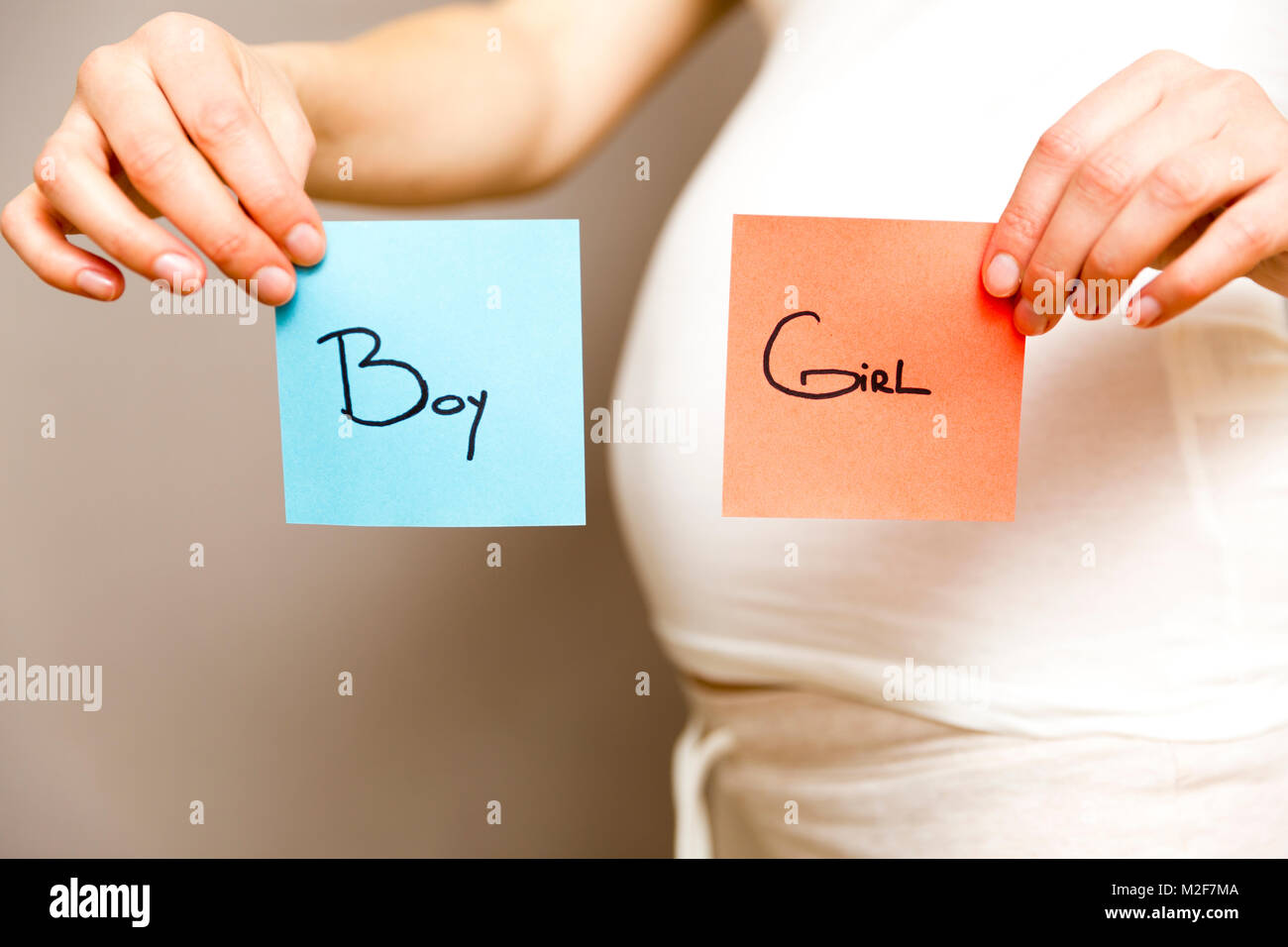hight resolution of pregnant woman holding blue and red post its with words boy and girl