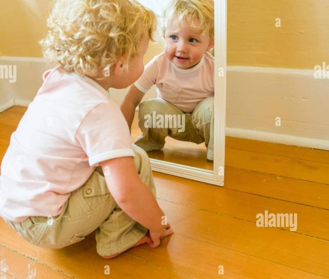 A Toddler Girl Playing And Looking At Herself In A Mirror