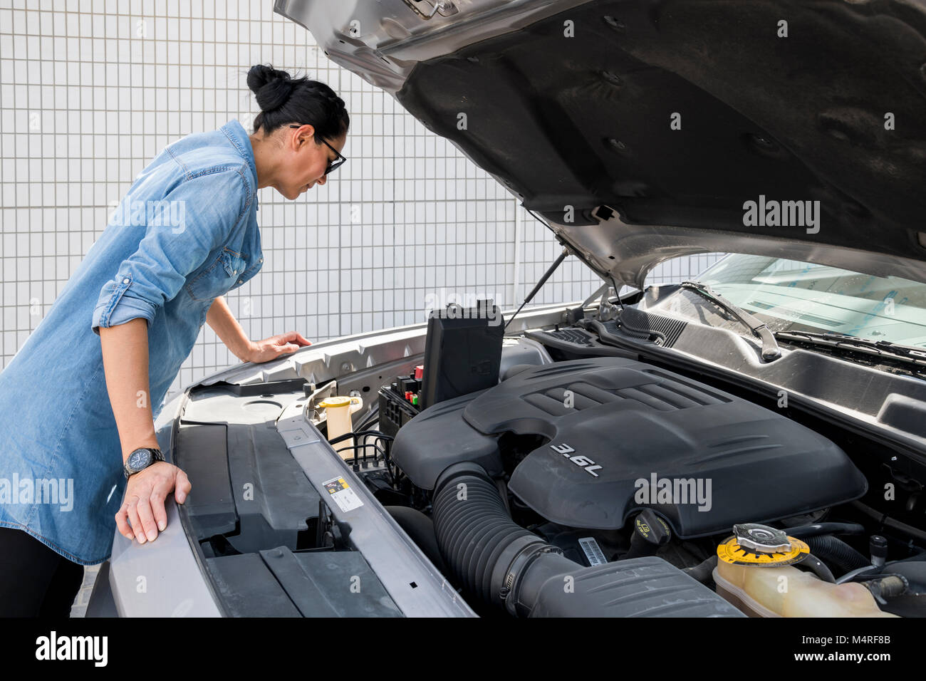 hight resolution of woman looking at fuse box of her sport car stock image
