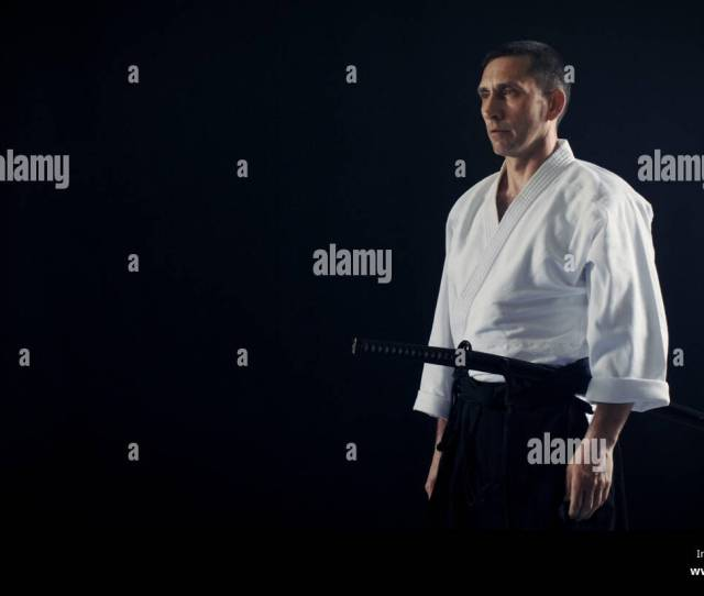 Portrait Shot Of The Aikido Master Wearing Traditional Samurai Hakama Clothes Holds His Japanese Sword Hes In The Spotlight Darkness Surrounds Him