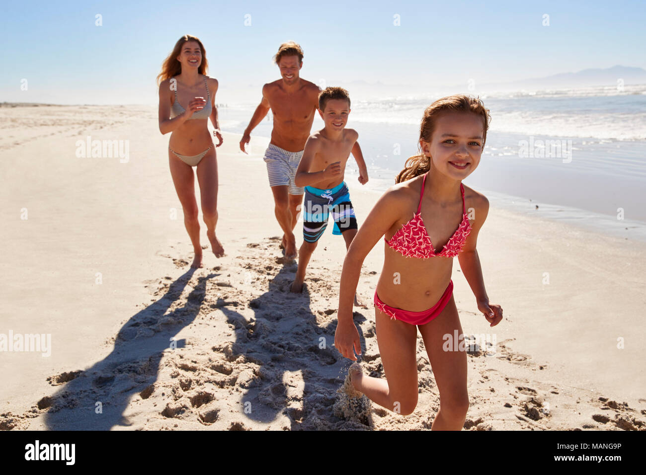 Family On Summer Vacation Running Along Beach Together Stock Photo Alamy