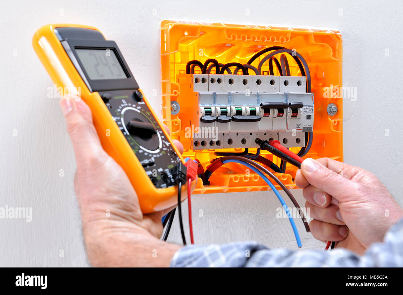 hight resolution of electrician technician working on a residential electrical panel measures the voltage on the terminals of