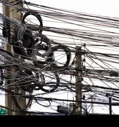 many wires messy with power line cables transformers and phone lines on old electricity pillar or utility pole at beside road in bangkok thailand [ 1300 x 956 Pixel ]