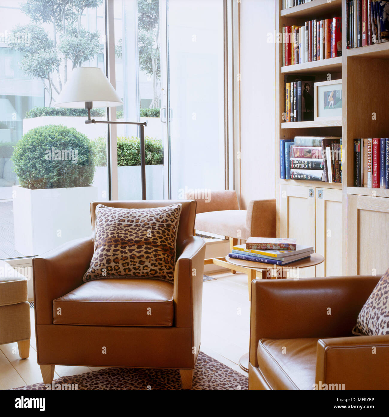 A Modern Sitting Room With Tan Leather Armchairs Bookcase