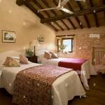A Country Guest Bedroom With Exposed Rustic Stone Walls And Beamed Ceiling Twin Single Beds Ceiling Fan Stock Photo Alamy