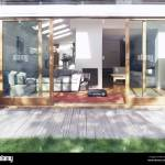Exterior Of A Modern House With Open Sliding Glass Doors To A Sunny Indoor Seating Area Stock Photo Alamy