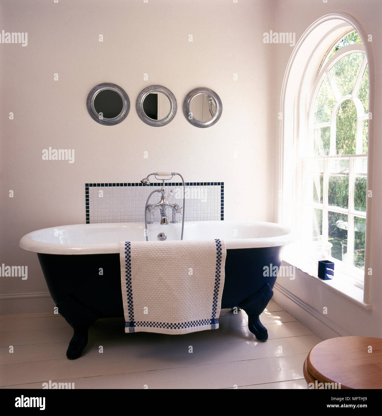 https www alamy com traditional bathroom with painted floorboards arched window freestanding roll top bathtub with mosaic tile backsplash and three circular mirrors image181864209 html