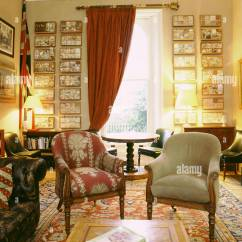 Traditional Living Rooms With Oriental Rugs Black Futon Room Sitting Red Draperies Upholstered Armchairs Rug Wooden Tables And A Collection Of Framed Shadow Boxes