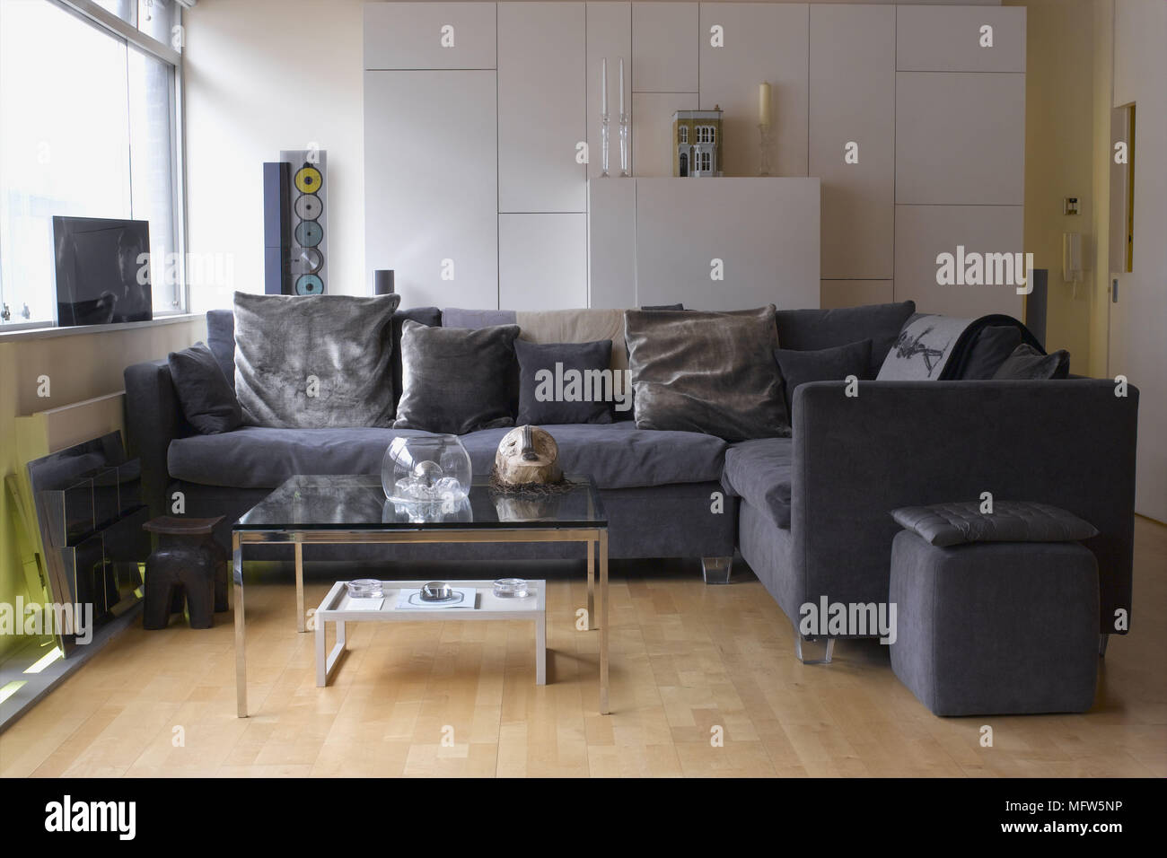 large square corner sofa light grey next a modern sitting room with glass coffee table wooden floor