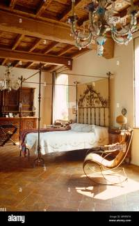 Antique wrought iron four poster bed in rustic bedroom ...