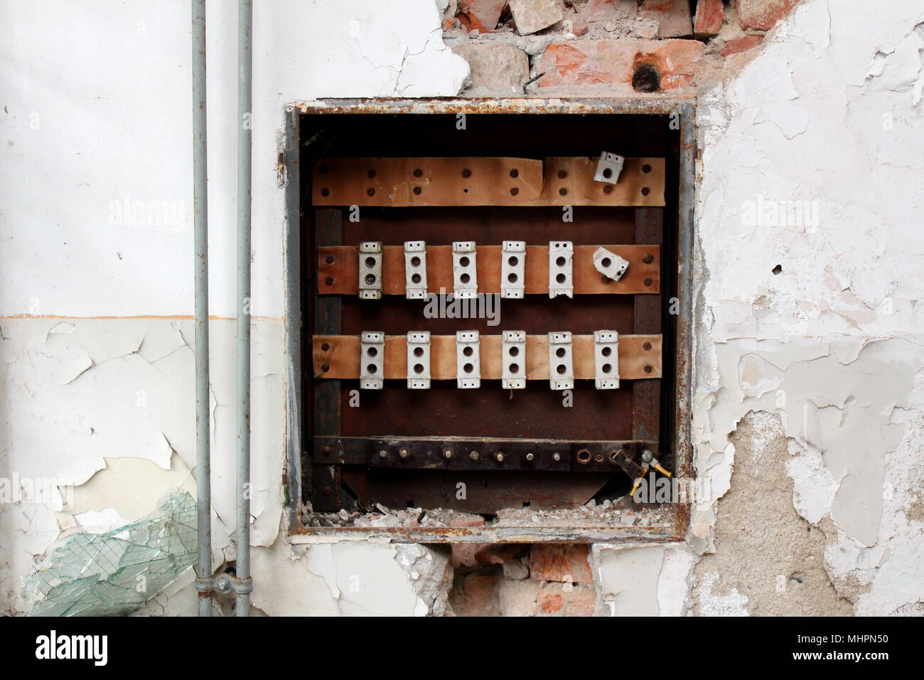 hight resolution of destroyed rusted old fuse box surrounded with crumbling wall visible bricks radiator pipes and