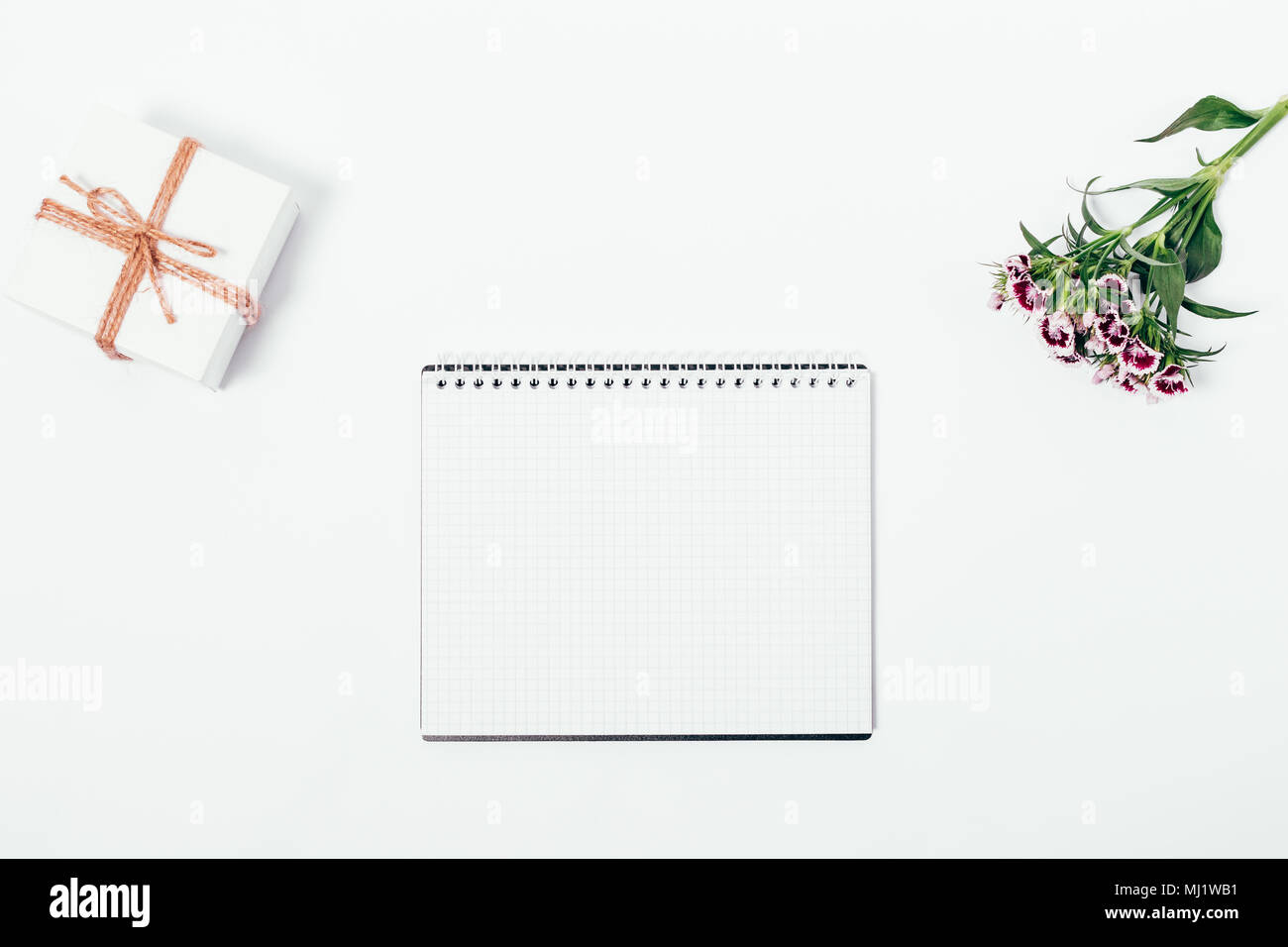 hight resolution of open blank notepad small gift box and flower on white table top view