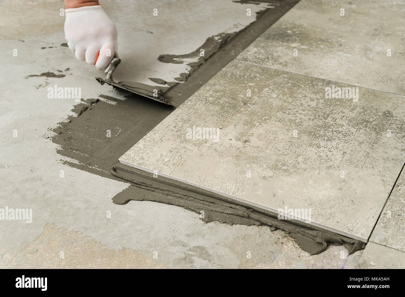 https www alamy com laying ceramic tiles troweling mortar onto a concrete floor in preparation for laying floor tile image184005881 html