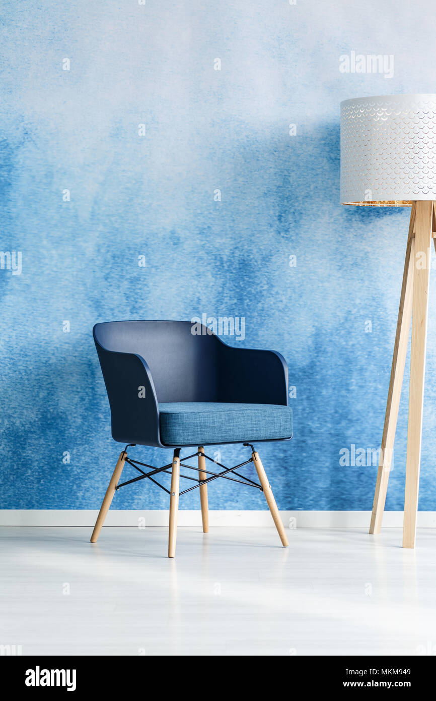 blue modern living room foot rests for navy armchair next to white wooden lamp in interior with ombre wall