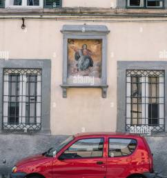 a tiny red car in front of an old building in lucca italy  [ 867 x 1390 Pixel ]